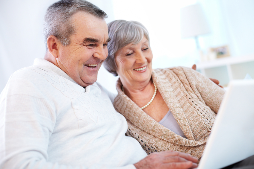 Couple smiling and looking at computer