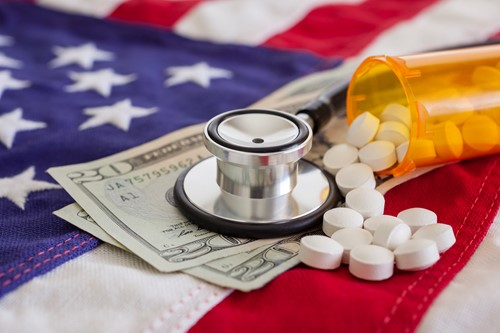 Stethoscope prescription drugs and money on an American flag