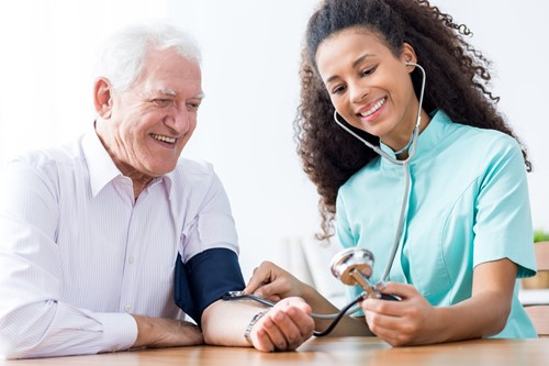 Man and nurse smiling in office while she checks blood pressure