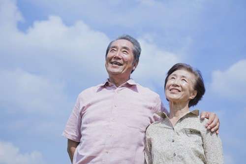 Smiling couple outside with sky background