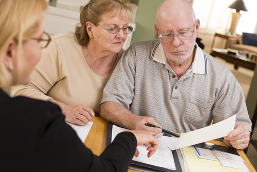 Couple reviewing paperwork with an adviser