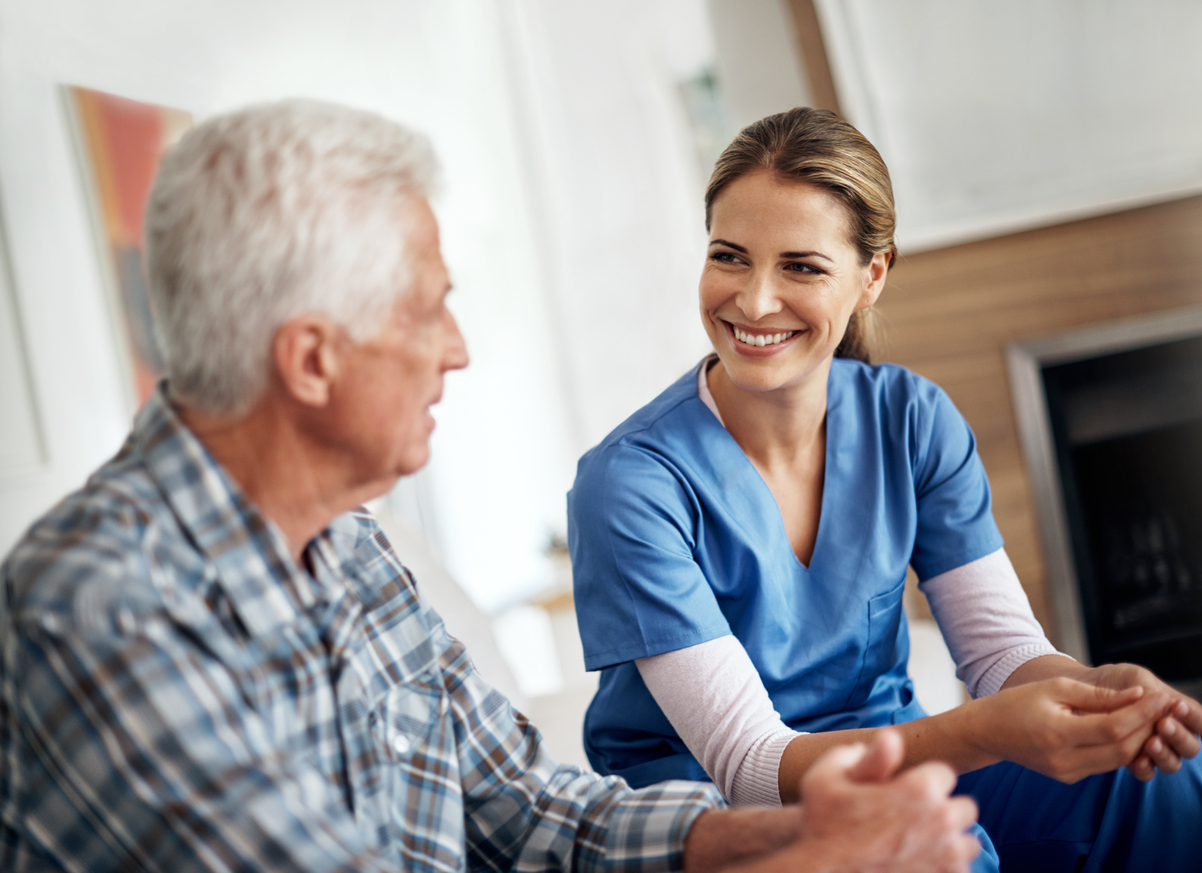 Smiling home health care nurse with a patient