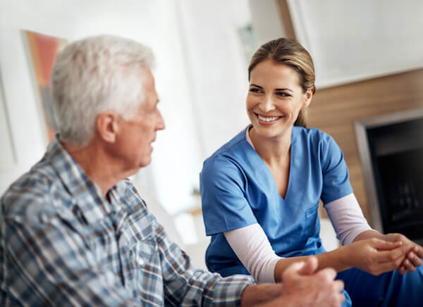 Smiling home health care nurse working with patient