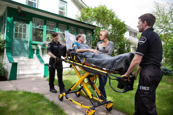 Woman taken out from her home on a stretcher with emergency crew
