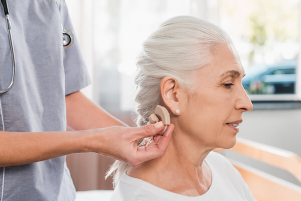 Woman getting a hearing aid from her doctor