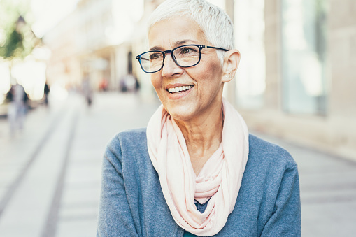 Woman wearing glasses and smiling outdoors