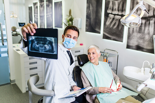 Woman looks at xrays with her dentist