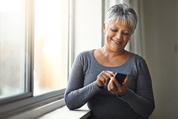 Woman smiles and uses her smartphone