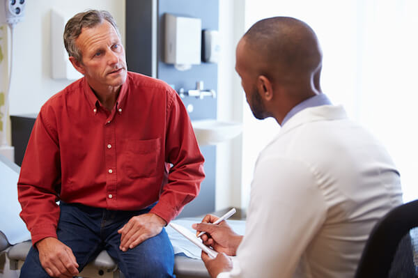 Doctor talks with his patient in hospital office