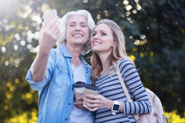 Two women holding coffee cups and taking a selfie outdoors
