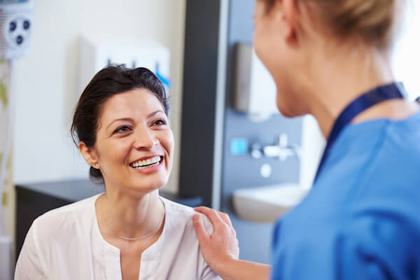 A woman smiles while speaking with her doctor