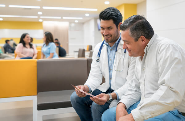 A man reviews information with his doctor in a hospital lobby