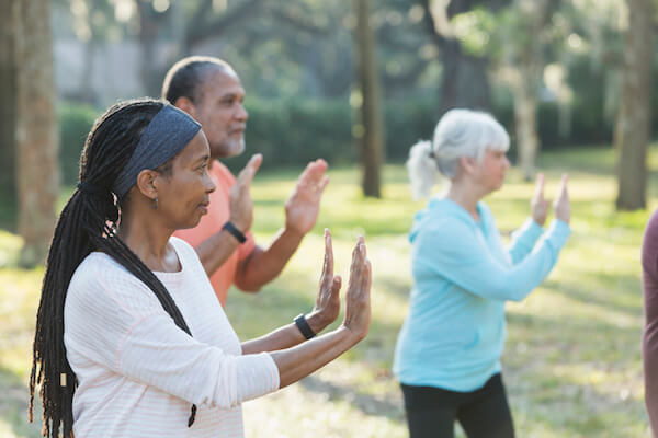 Older adults do tai chi outside in a park
