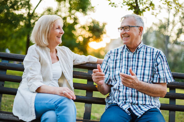 Smiling couple looking talking and sitting on a park bench