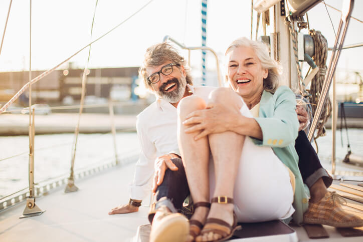 Smiling couple sits on a sailboat on a sunny day